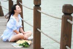 La mujer hermosa joven china se sienta en el puente ve el lago en parque Imagen de archivo libre de regalías