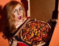 La mujer hermosa joven come la pizza entera vegetariana mexicana en caja en naranja fotos de archivo