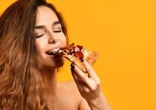 La mujer hermosa joven come la rebanada de pizza de salchichones con los ojos cerrados que sonríe en amarillo fotos de archivo