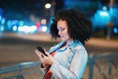 La mujer hermosa joven con el pelo afro muy rizado usando el teléfono móvil en la noche iluminó la calle Muchacha de moda inusual fotos de archivo libres de regalías