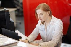 La mujer hermosa joven con el pelo rojo, vidrios que llevan, trabajando en la oficina, utiliza un ordenador portátil y un teléfon fotos de archivo