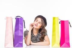 La mujer hermosa joven con los panieres en la tabla satisfizo y tiene resto con sonrisa feliz en el fondo blanco imágenes de archivo libres de regalías