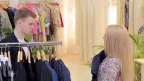 La mujer hermosa joven con su novio elige la tienda del clother almacen de video