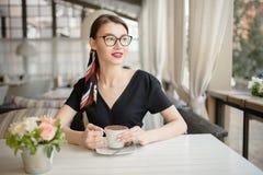 La mujer hermosa joven con una sonrisa se sienta en la calle y el café de las bebidas Café brillante del verano imagen de archivo