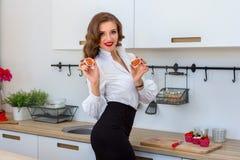 La mujer hermosa joven corta un higo en cocina Imagen de archivo libre de regalías