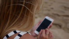 La mujer hermosa joven de Defocus delgada con el pelo rubio largo en vestido blanco y negro se está sentando en la playa y está u almacen de metraje de vídeo