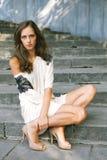 La mujer hermosa joven de la mujer se sienta en pasos de progresión Fotos de archivo libres de regalías