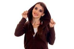 La mujer hermosa joven del estudiante en deportes marrones viste con la capilla que sonríe en la cámara aislada en el fondo blanc Imagen de archivo libre de regalías