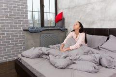 La mujer hermosa joven despertó y sentándose en el paj que llevaba de la cama Fotos de archivo