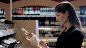 La mujer hermosa joven elige el vino en el supermercado Morenita en tienda alcohólica almacen de video