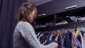 La mujer hermosa joven elige la ropa para el evento especial en su vestuario almacen de video