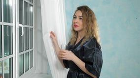 La mujer hermosa joven en bata de casa est? mirando hacia fuera la ventana por la tarde metrajes