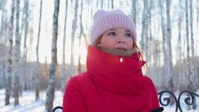 La mujer hermosa joven en chaqueta caliente roja se sienta en banco en parque ilustrado con los abedules y calienta las manos en  almacen de metraje de vídeo