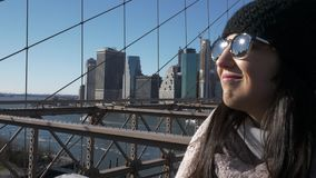La mujer hermosa joven en el puente de Brooklyn Nueva York disfruta de un día soleado maravilloso almacen de metraje de vídeo