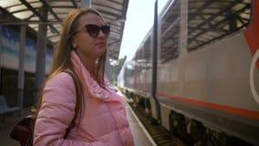 La mujer hermosa joven en la estación de tren está esperando el aterrizaje del tren metrajes