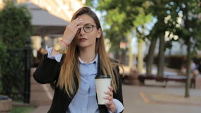 La mujer hermosa joven en traje con la bebida para llevar está caminando en la calle almacen de video