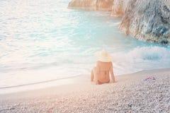La mujer hermosa joven en traje de baño y el sombrero que se relaja en Navagio varan, isla de Zakynthos, Grecia Foto de archivo