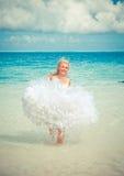 La mujer hermosa joven en un vestido de la novia corre en las ondas del mar, con un efecto retro imagen de archivo libre de regalías