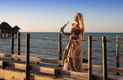La mujer hermosa joven en un vestido largo en el camino de madera sobre el mar Imagen de archivo