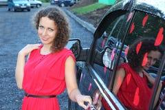 La mujer joven en vestido se coloca cerca para ennegrecer el offroader mojado Imagenes de archivo