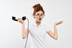 La mujer hermosa joven en vidrios en un fondo del blanco sostiene un receptor de teléfono fijo Imagen de archivo