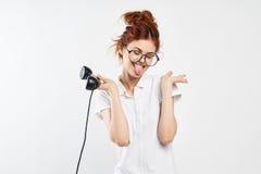 La mujer hermosa joven en vidrios en un fondo del blanco sostiene un receptor de teléfono fijo Fotografía de archivo libre de regalías