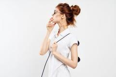 La mujer hermosa joven en vidrios en un fondo del blanco sostiene un teléfono fijo, moda, comunicación Imágenes de archivo libres de regalías