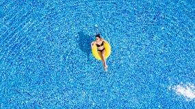 La mujer hermosa joven es relajante en piscina con el anillo amarillo de goma imágenes de archivo libres de regalías