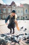 La mujer hermosa joven está alimentando palomas con las migas de pan en la plaza Imágenes de archivo libres de regalías