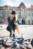 La mujer hermosa joven está alimentando palomas con las migas de pan en la plaza Imagen de archivo