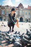 La mujer hermosa joven está alimentando palomas con las migas de pan en la plaza Imagenes de archivo