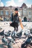 La mujer hermosa joven está alimentando palomas con las migas de pan en la plaza Imagen de archivo libre de regalías