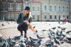 La mujer hermosa joven está alimentando palomas con las migas de pan en la plaza Foto de archivo