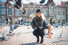 La mujer hermosa joven está alimentando palomas con las migas de pan en la plaza Fotografía de archivo