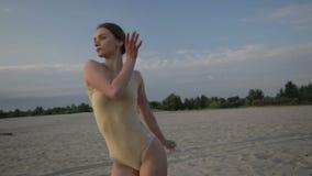 La mujer hermosa joven está bailando el traje del cuerpo que lleva en salida del sol en el desierto almacen de metraje de vídeo