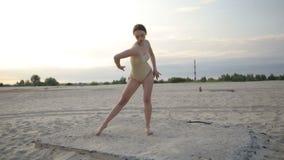 La mujer hermosa joven está bailando el traje del cuerpo que lleva en salida del sol en el desierto metrajes