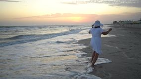 La mujer hermosa joven está caminando por el mar en la puesta del sol En un vestido blanco y un sombrero blanco La mujer está emb almacen de metraje de vídeo