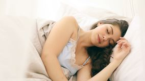 La mujer hermosa joven está durmiendo en las hojas de cama cómodas Imágenes de vídeo almacen de metraje de vídeo