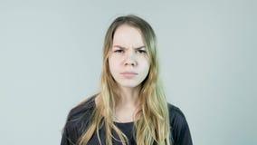 La mujer hermosa joven está enojada en un fondo blanco Mujer joven enojada metrajes