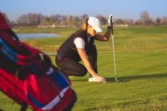 La mujer hermosa joven está entrenando a golf fotografía de archivo libre de regalías