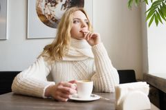 La mujer hermosa joven está sonriendo en café y está disfrutando del aroma del café fotografía de archivo libre de regalías