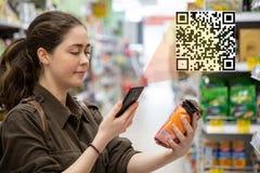 La mujer hermosa joven explora un producto del código de QR en el supermercado El concepto de tecnolog?a moderna imágenes de archivo libres de regalías