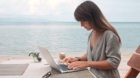 La mujer hermosa joven feliz acabó su trabajo en ordenador portátil en la playa metrajes
