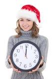 La mujer hermosa joven feliz en ropa del invierno y el sombrero de santa se sostienen Imágenes de archivo libres de regalías
