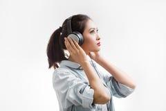 La mujer hermosa joven goza el escuchar la música con los auriculares grandes aisló el fondo blanco Imagen de archivo libre de regalías