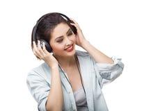 La mujer hermosa joven goza el escuchar la música con los auriculares grandes aisló el fondo blanco Fotografía de archivo libre de regalías