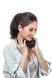 La mujer hermosa joven goza el escuchar la música con los auriculares grandes aisló el fondo blanco Fotos de archivo