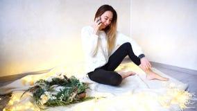 La mujer hermosa joven habla en el teléfono el Nochebuena y sienta o Imágenes de archivo libres de regalías