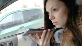 La mujer hermosa joven habla un mensaje de la voz en un teléfono móvil que se sienta en el coche almacen de video