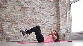 La mujer hermosa joven hace crujidos en el gimnasio metrajes